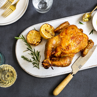whole roast chicken with grilled lemon and fresh rosemary on a white platter on a black background