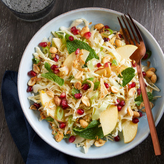 Winter cabbage and apple salad with nuts and dried fruit in a white bowl with a copper fork.