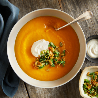 Bowl of orange winter squash and coconut bisque topped with sour cream and a green garnish in a white bowl on a wooden table.