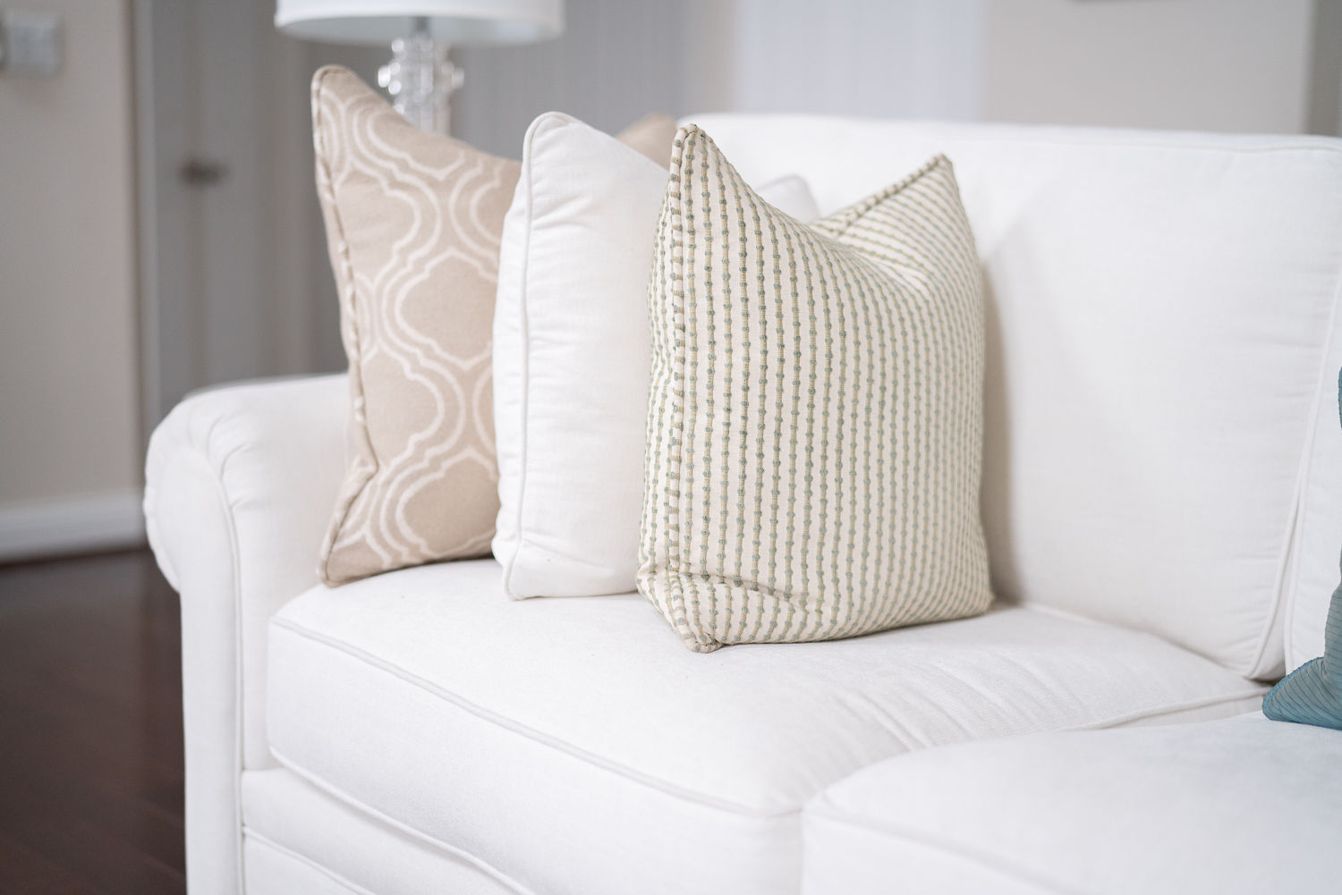 Neutral-themed pillowcases made from decorative rugs on a white sofa