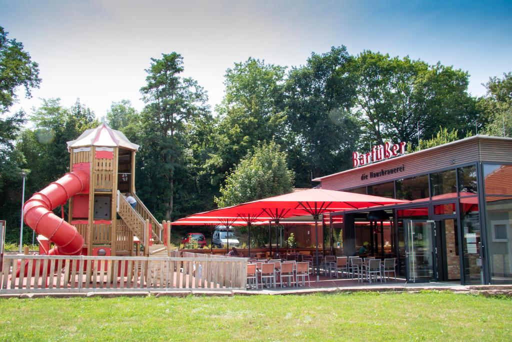 Restaurant von Außen mit vier roten Sonnenschirmen auf der Terrasse