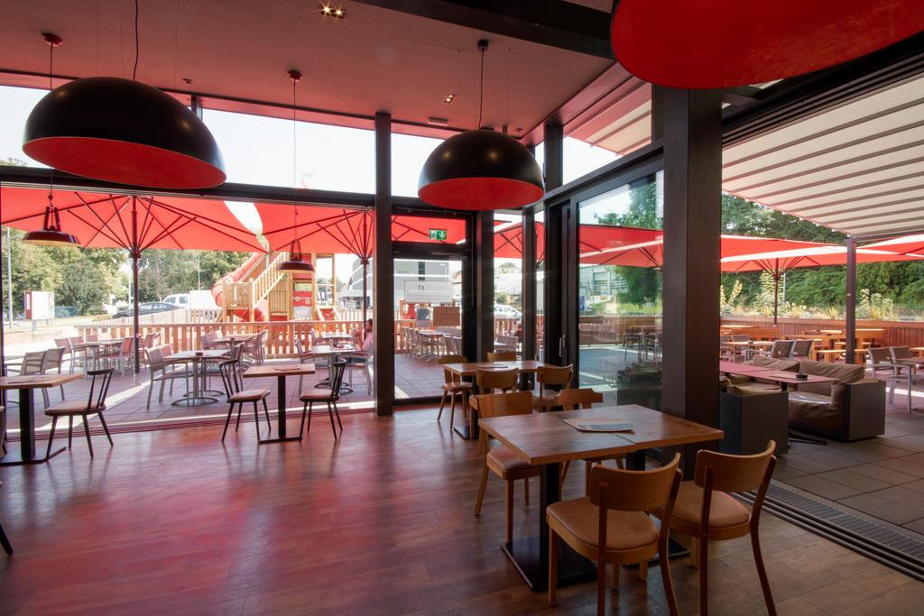 Restaurant von Innen mit vier roten Sonnenschirmen auf der Terrasse
