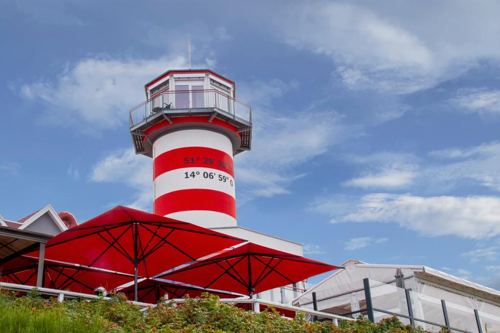Terrasse mit roten Sonnenschirmen und Leuchtturm in Hintergrund