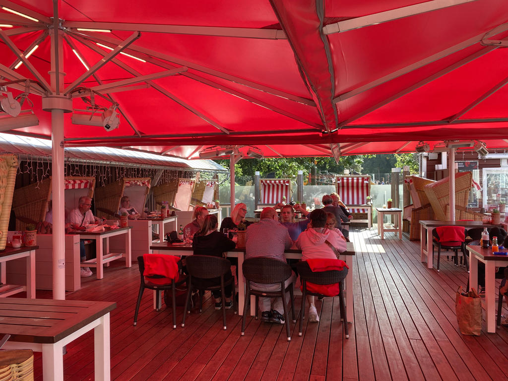 Patio at the sea with red parasols