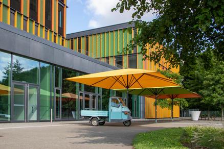 Schule mit spielenden Kindern und grünen und orangenen Sonnenschirmen