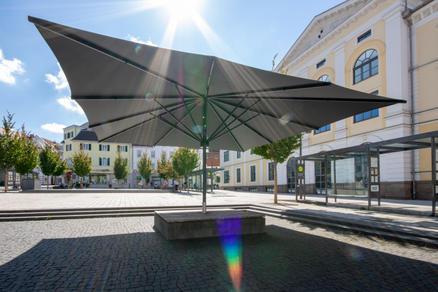 Öffentlicher Platz mit einem dunklen Sonnenschirm