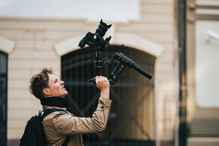 Man holding Zhiyun Crane 3S with camera mounted
