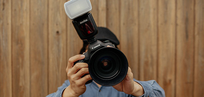 Man hold camera with Speedlight attached