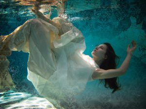 Woman in white dress floating underwater