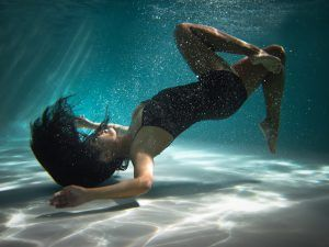 Woman in swimsuit floating underwater