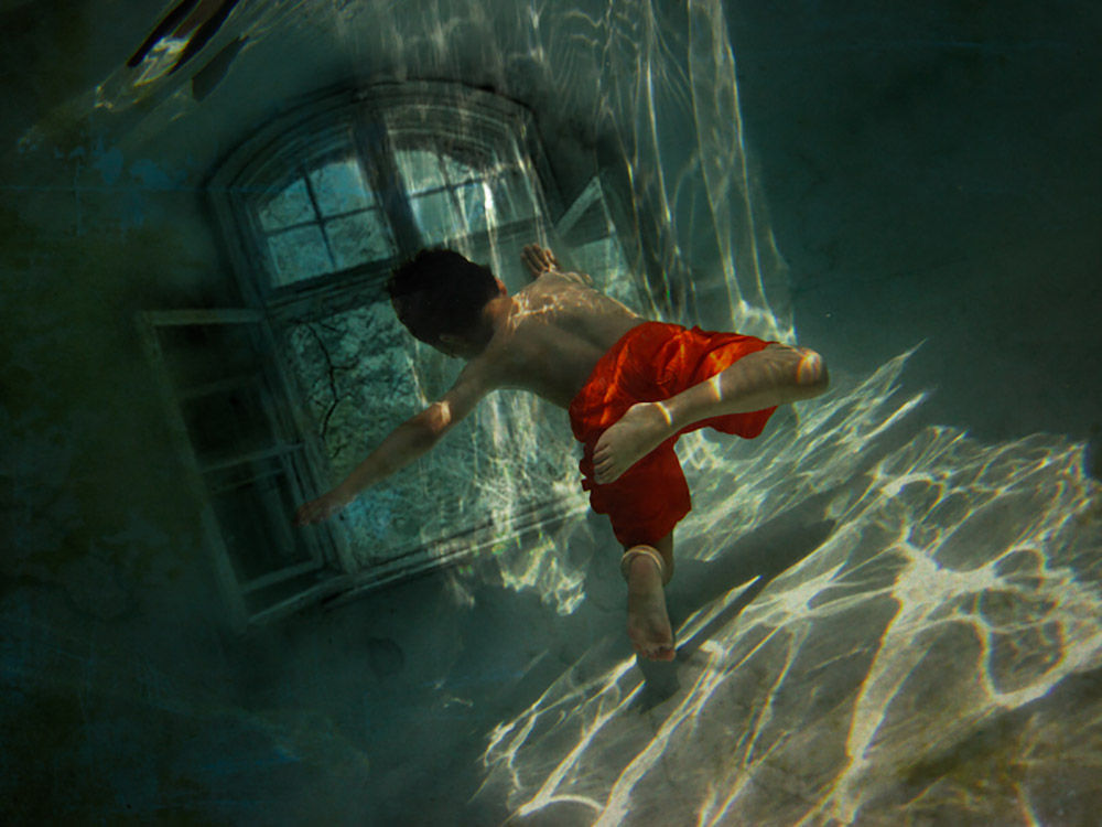 Boy floating in at a window at the bottom of a pool