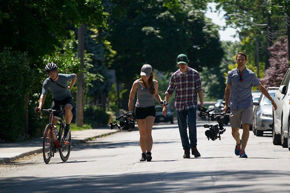 Film crew walking down the road
