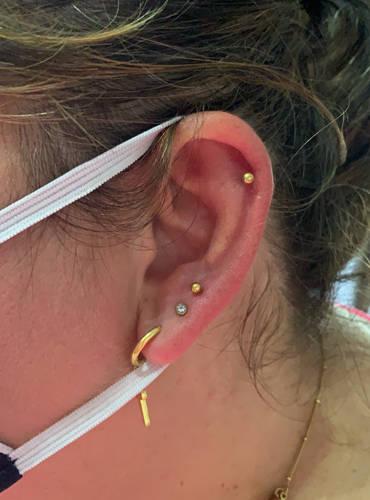 Verschiedene Piercings im rechten Ohr einer Kundin.