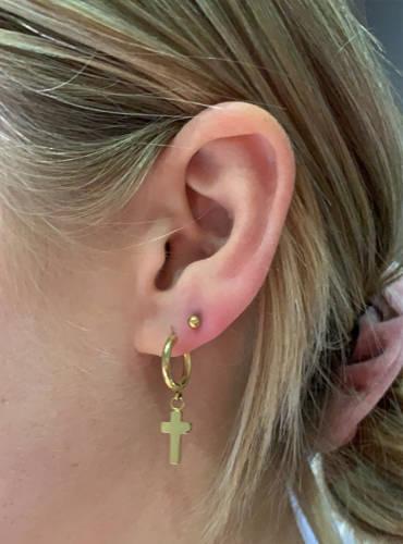 Ohrpiercing mit Kreuz Ohring bei einer Frau am rechten Ohr.