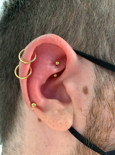 Fünf Piercings im Ohr bei einem Mann.