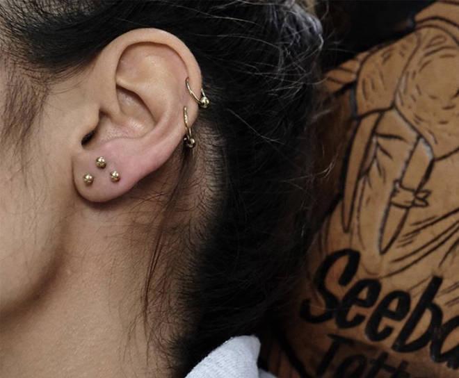 Piercing Kundin mit mehreren Ohrpiercings im Ohr.