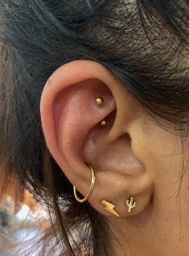 Ein Piercing im linkem Ohr einer Frau