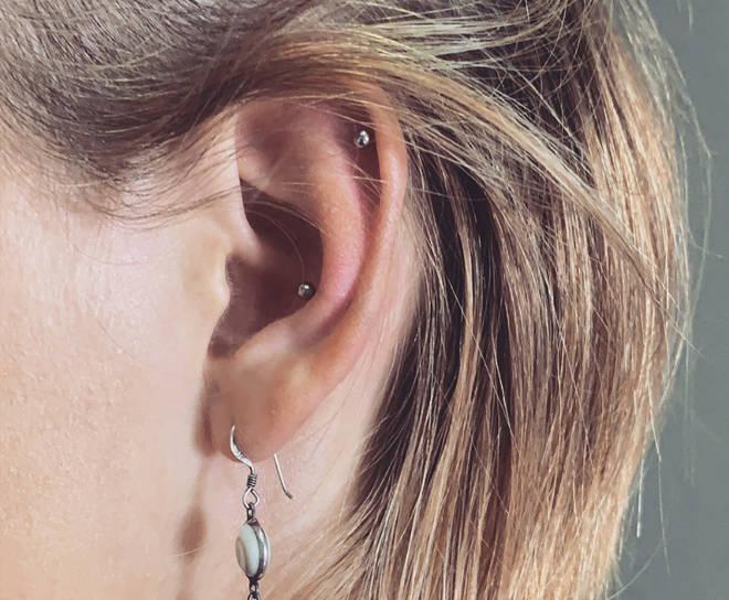 Piercings in den Ohren mit einem Ohrring.