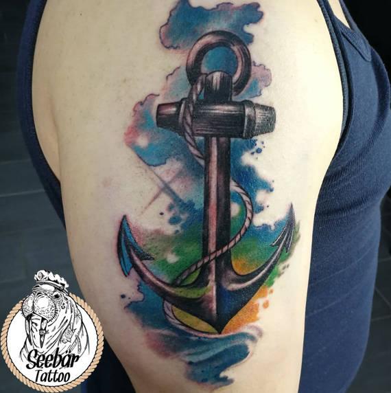 Der Watercolor-Stil mit einem Anker tättowiert auf dem Oberarm.