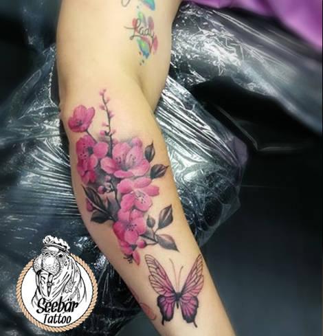 Watercolortattoo auf dem Unterarm mit Blumen.