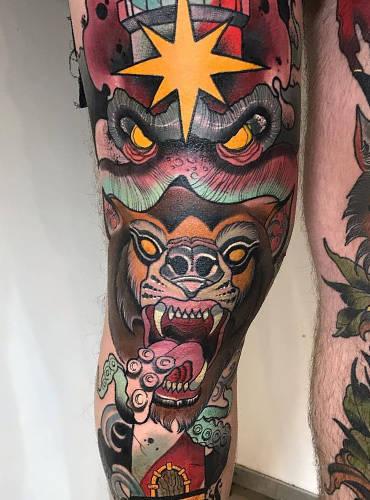 Bein tättowiert in bunten Tattoos mit vielen Tattoomotiven drauf.