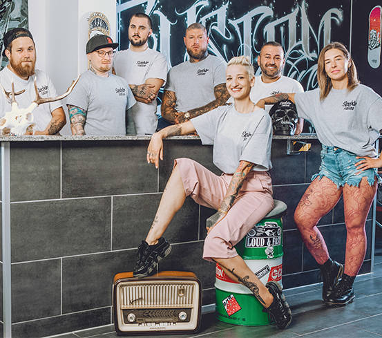 Seebaer Tattoo Artist Kiel Team sitzt zusammen mit den Sieben Tattoo Künstlern und den Piercing Mädels am Tresen