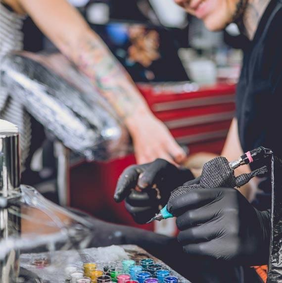 Tattookünstler während der Arbeit mit einer Kundin