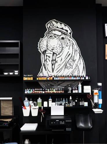 Das Seebär Logo als Wandaufhänger hängt über einer reihe von Tattoofarben.