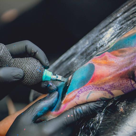 Tattoo Artist aus Kiel während der Tattooarbeit mit der Maschine.