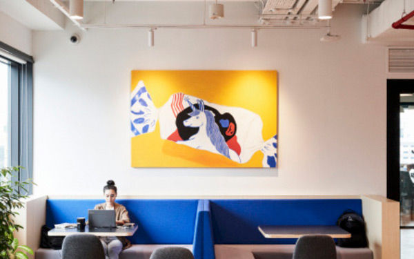 High ceiling office space with woman sitting in a private booth with blue cushions