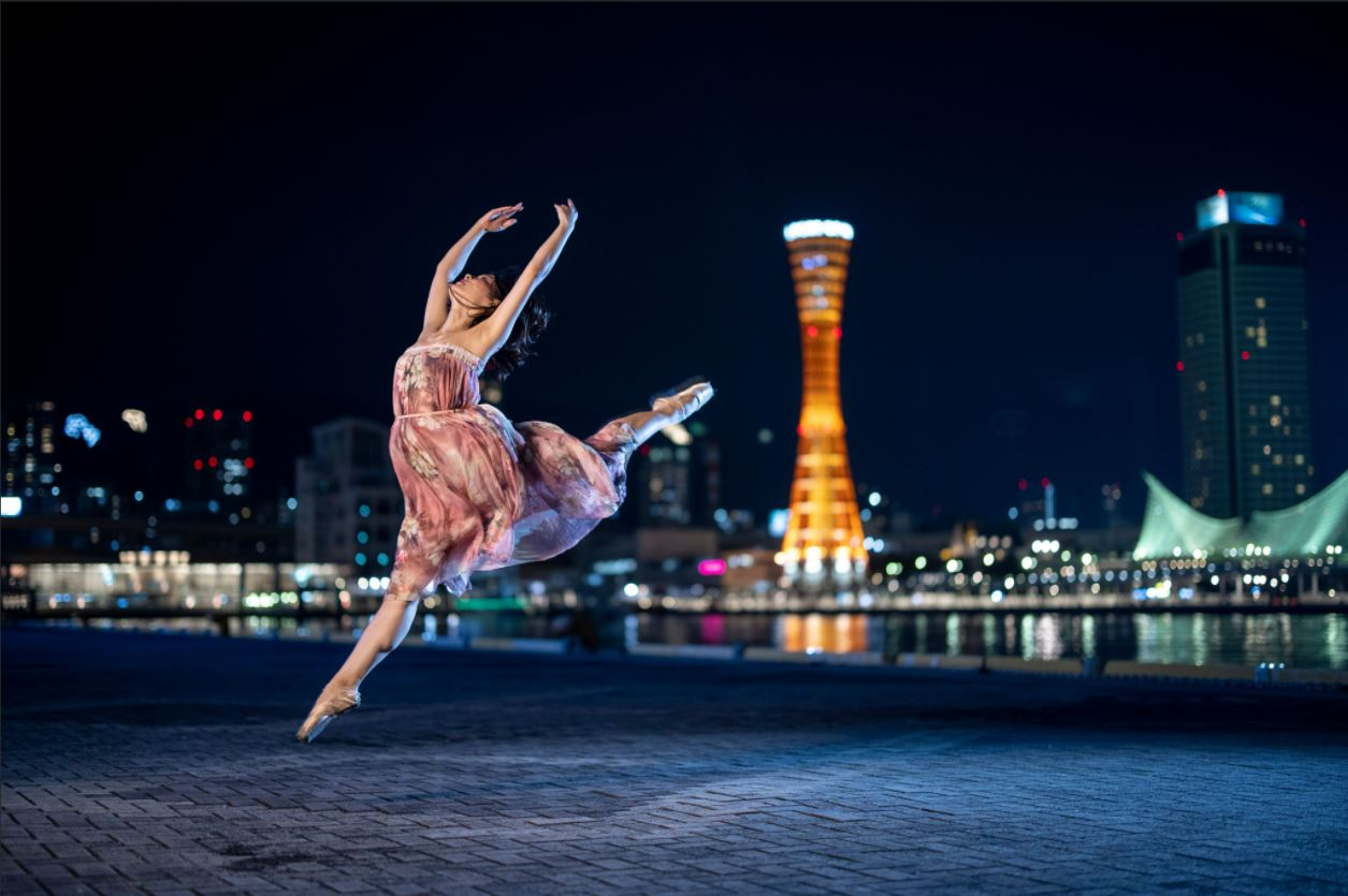 Ballerina leaping, arms outstretched, with city lights in the background, photographed using the Canon Speedlite EL-1 Flash