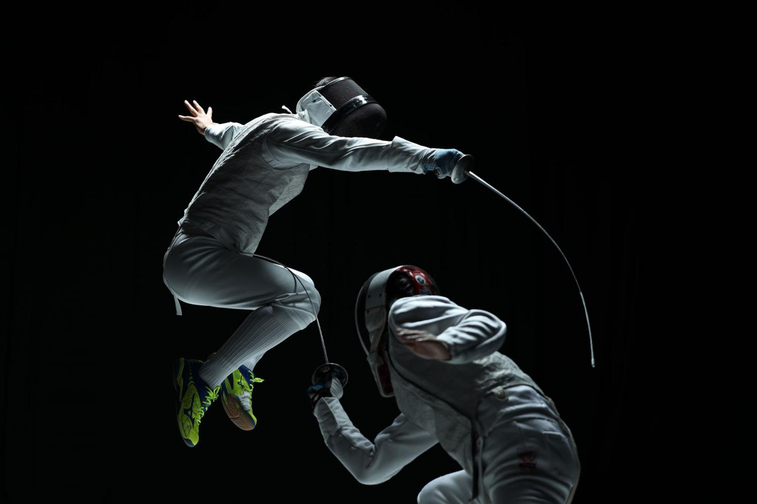 Two competitive fencers mid-combat against a black background, photographed with the Canon RF 70-200mm f2.8L IS USM lens