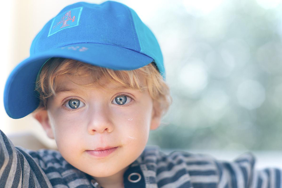 Blonde-haired, blue-eyed boy wearing a blue cap and striped top, photographed with the Nikon AF-S NIKKOR 85mm f/1.4G Lens