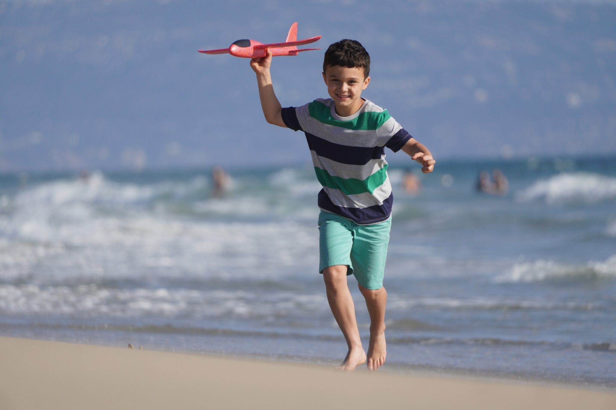 Boy in striped T-shirt running along beach with toy the plane in hand, shot using the Sony E 70- 350mm f4.5-6.3 G OSS Lens