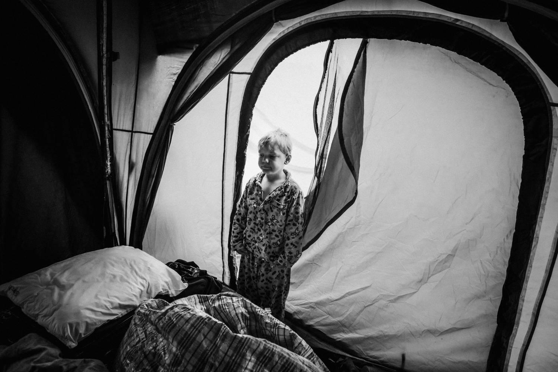 a boy standing inside a tent