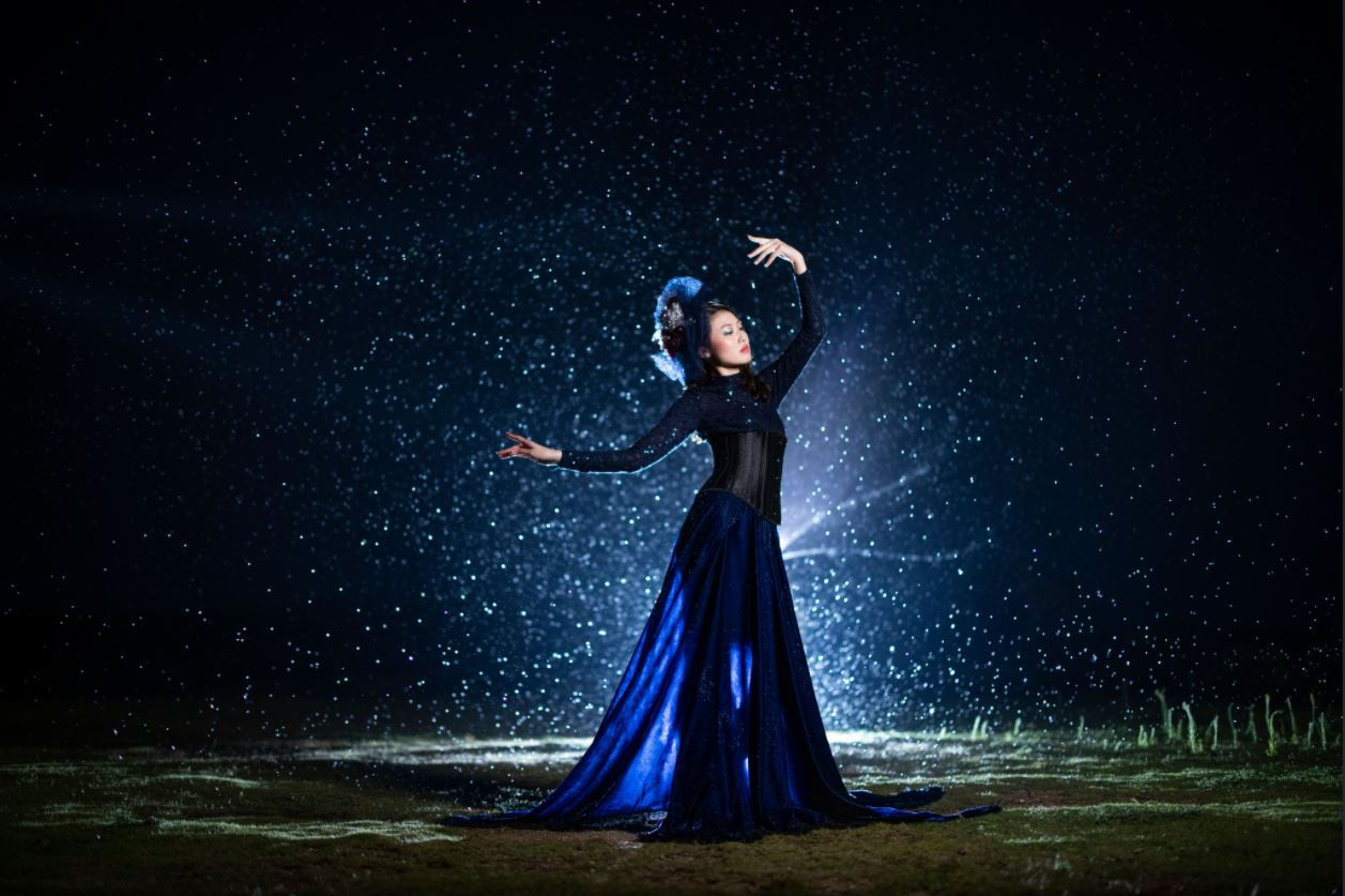 Fashion model in dark blue gown posing in front of a burst of white dots, photographed using the Canon Speedlite EL-1