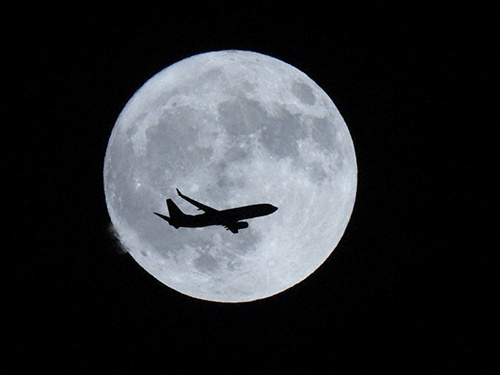 Aeroplane silhouetted against a much larger moon, photographed using the Nikon Coolpix P950