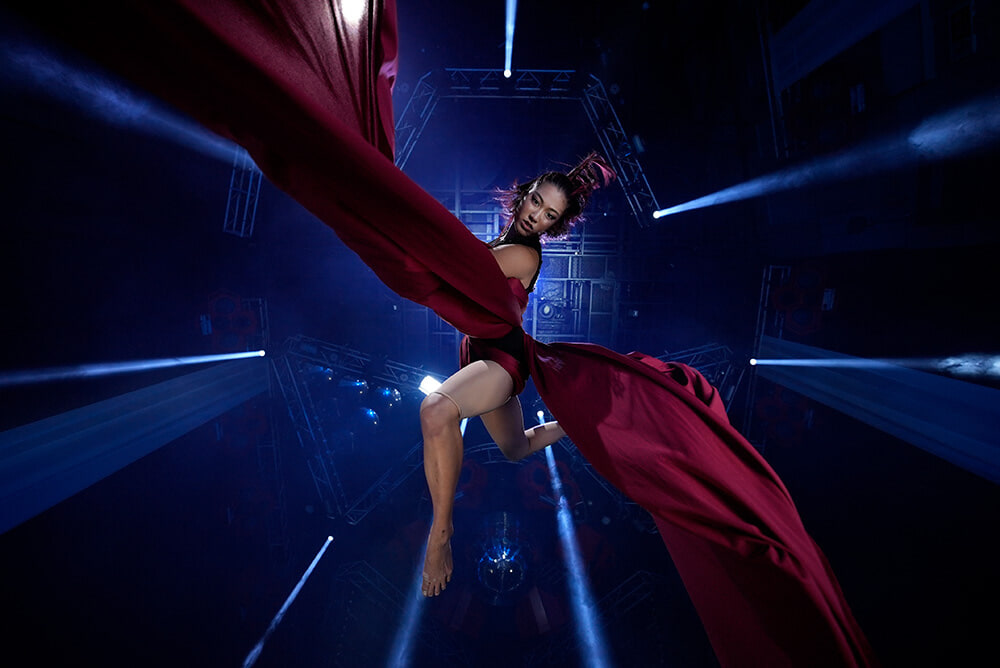 Curtain dancer suspended by billowing maroon silk, shot from below with the Sony a7s III