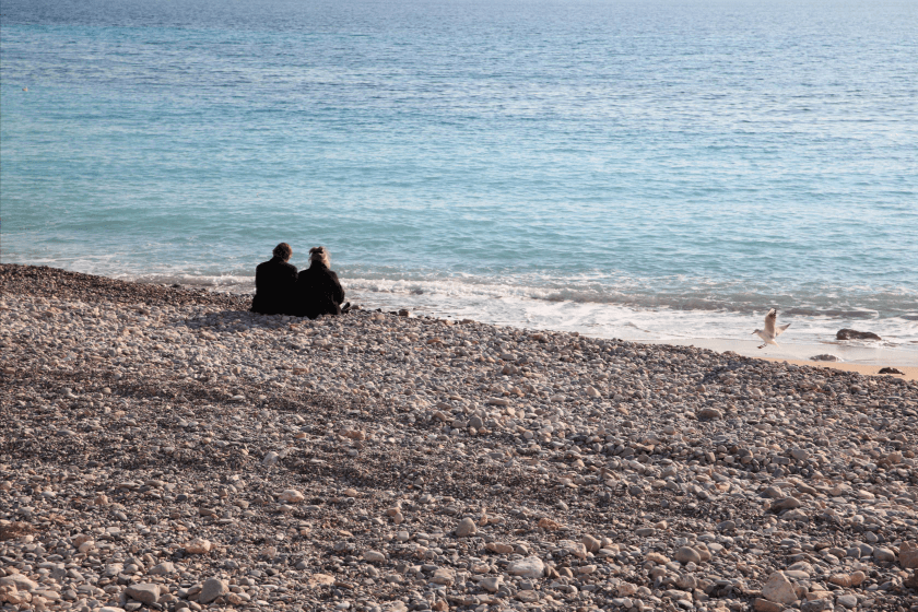 Couple sitting on a pebble beach, looking out to sea - photographed with the Canon EF 24-70mm f2.8L II USM lens