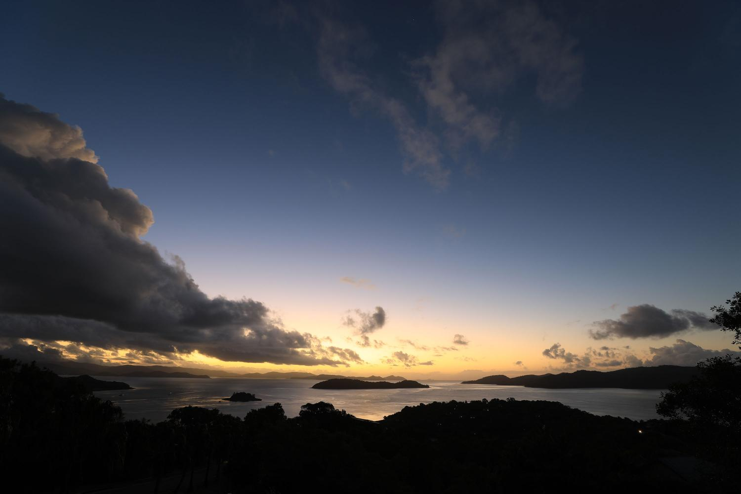 Sun setting behind islands and mountains in the distance, photographed with the Canon EF 16- 35mm f/2.8L III USM Lens