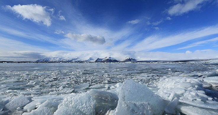 Arctic seascape with ice-filled water beneath a cloudy blue sky, photographed with the Canon 16-35mm f4 lens
