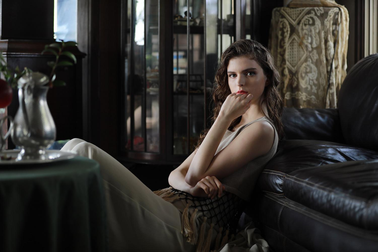 Long-haired young woman in elegant dress reclining against a leather couch, photographed with the Canon 70-200mm f2.8L IS III