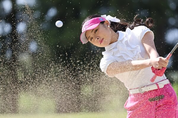 Female golfer watching a ball as she completes her swing, photographed with the Canon RF 100-500mm f4.5-7.1 L IS USM Lens