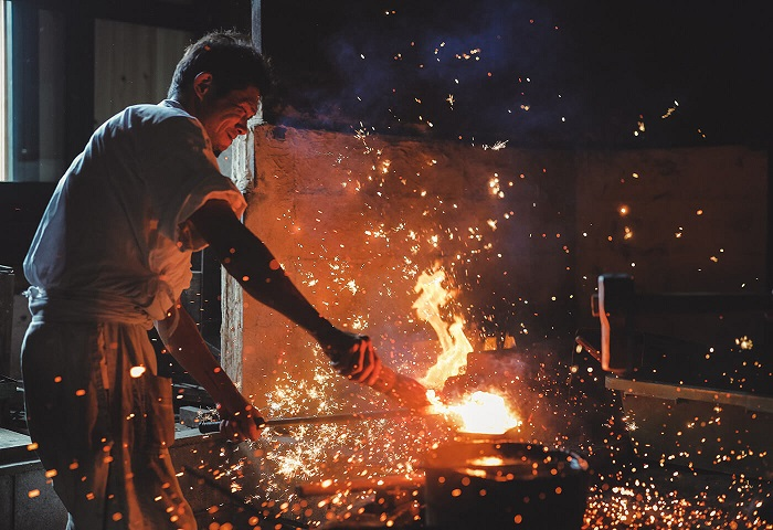 Sparks flying around a Japanese sword maker forging a blade, photographed with the Canon RF 24-105mm f4 IS USM lens