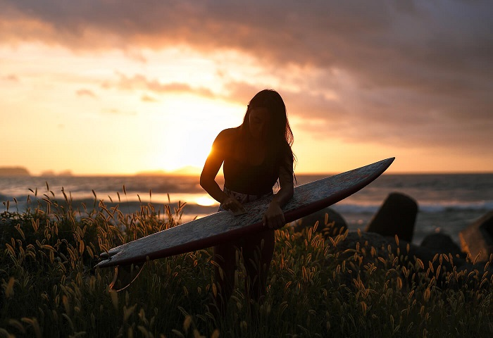 Woman waxing a surfboard among tall grass, sun setting over the ocean behind, shot with the Canon RF 50mm f1.2L USM lens