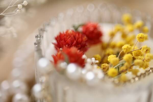 Shallow-focus close-up of red and yellow flowers in a glass vase, photographed with the Canon RF 85mm f2 Macro IS STM lens