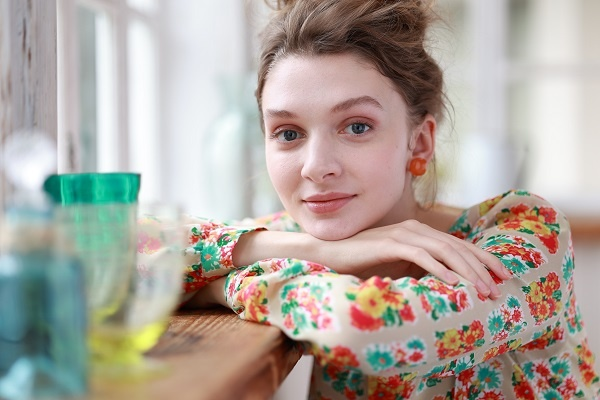 Smiling young woman in floral top resting on the edge of a wooden table, shot with the Canon RF 85mm f2 Macro IS STM lens