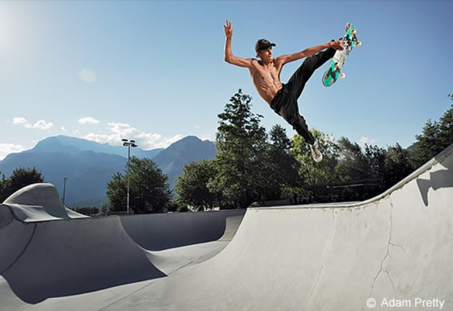 Skateboarder suspended mid-air against a blue sky above a halfpipe, photographed with the Panasonic LUMIX S5