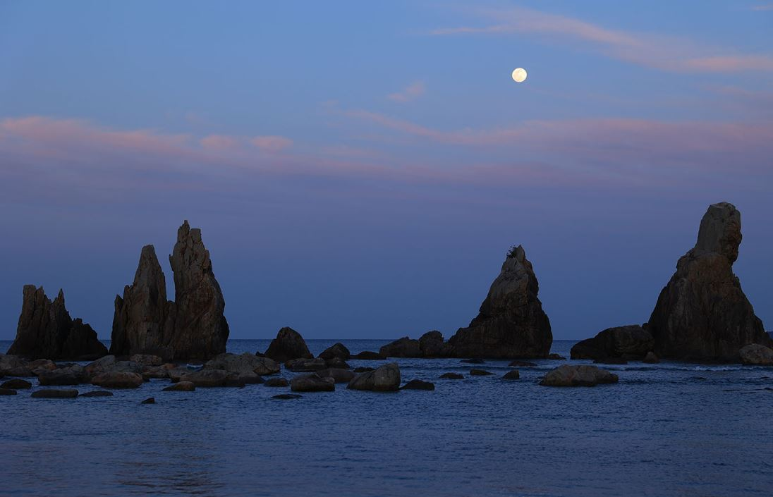 Jagged rocks rising from the sea beneath the moon and darkening sky, photographed with the Canon EOS R6 mirrorless camera
