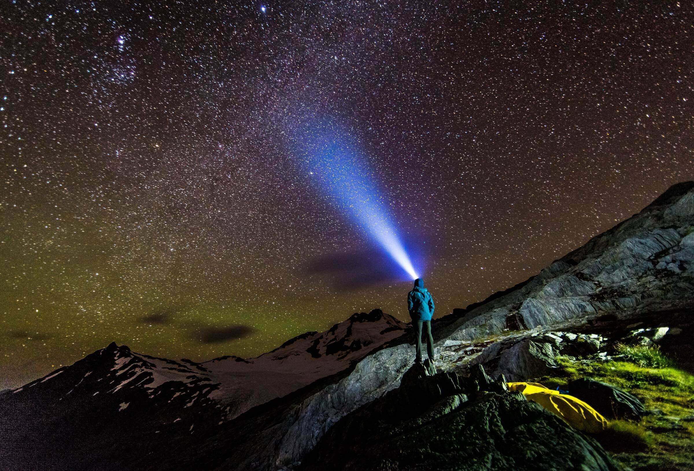Self portrait looking up towards Mount Brewster in the New Zealand Southern Alps. Thegreen glow in the sky is a faint Aurora Australia.